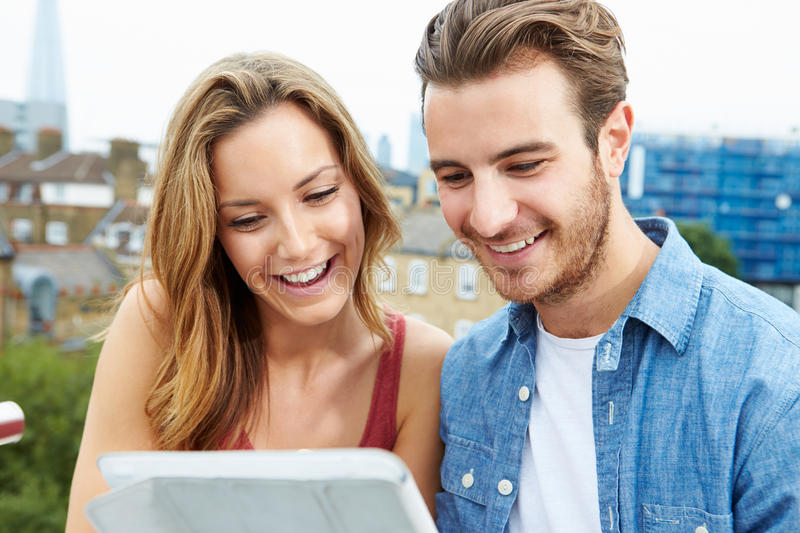 Couple On Roof Terrace Using Digital Tablet. Close Up Of Couple On Roof Terrace Using Digital Tablet Smiling stock photos