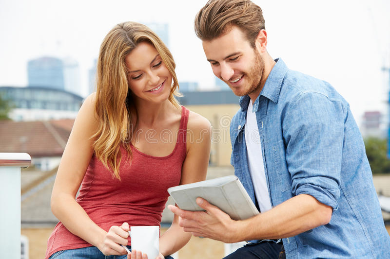 Couple On Roof Terrace Using Digital Tablet. To Browse The Web stock photos