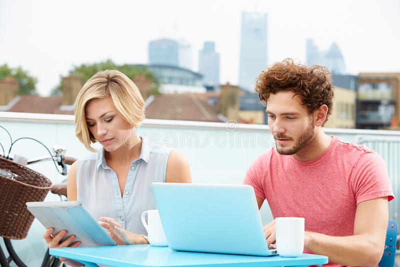 Couple On Roof Terrace Using Laptop And Digital Tablet. Sitting Down Browsing The Net stock photography