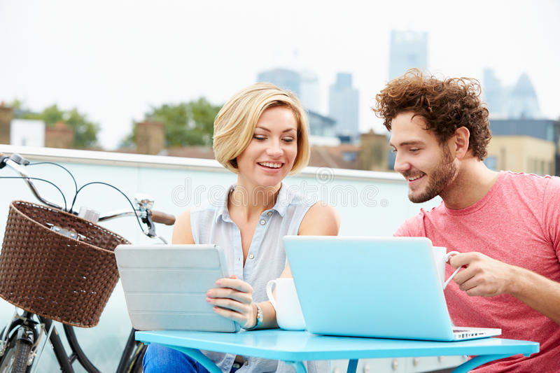 Couple On Roof Terrace Using Laptop And Digital Tablet. Sitting At Table With Bike In Background stock images