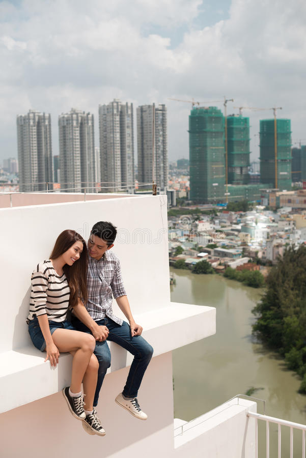 Couple on the roof. Young Vietnamese couple sitting on the edge of the roof stock photo