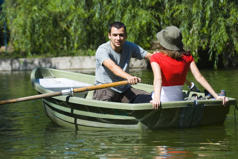Couple in rowboat. Man is rowing while woman is relaxing