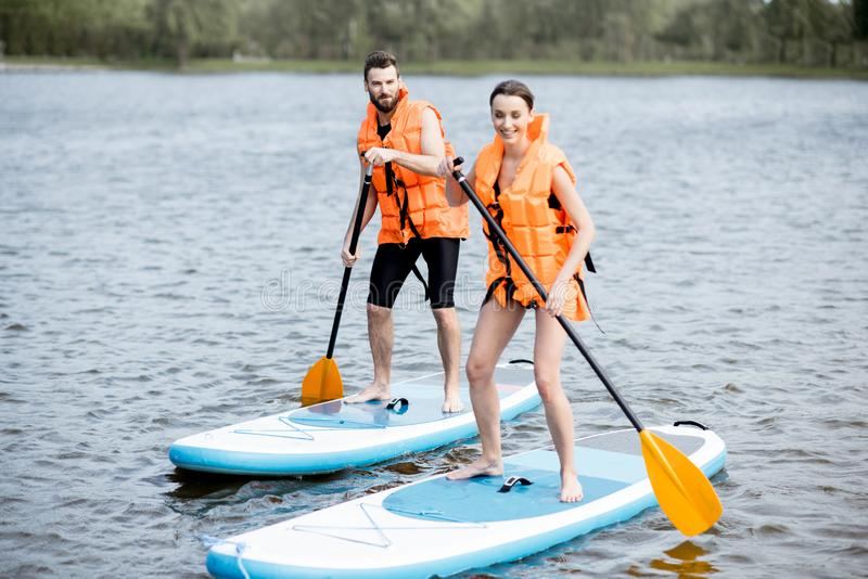 Couple Rowing On The Stand Up Paddleboard Stock Photo ...