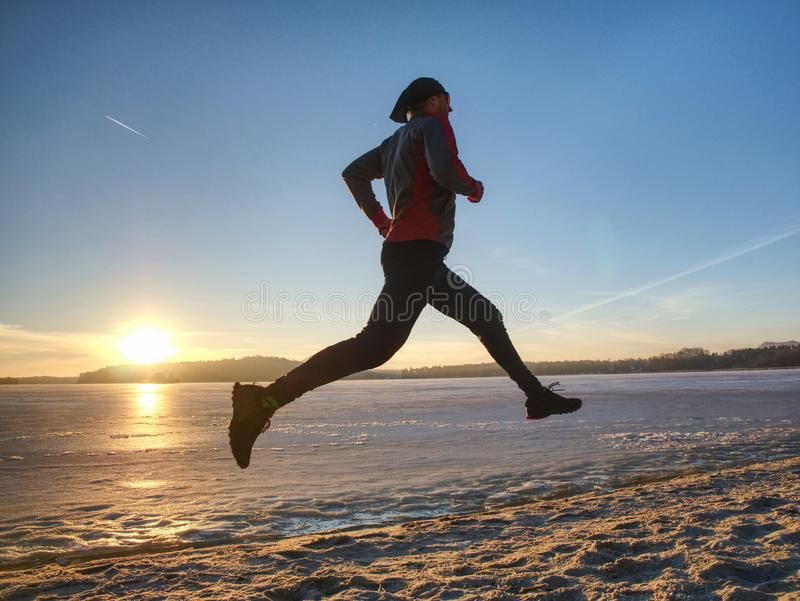 Couple runners running in winter nature. Frozen river royalty free stock photography
