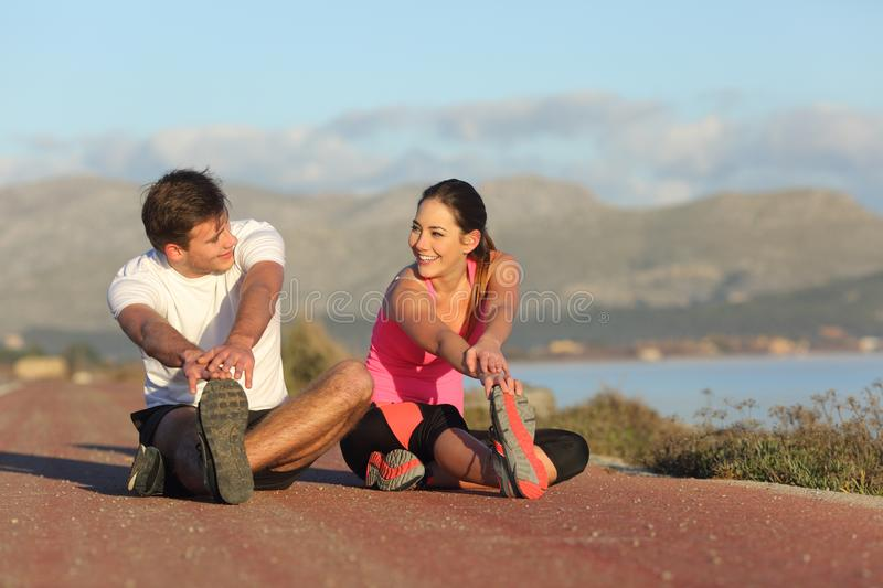 Couple of runners stretching legs after sport stock images