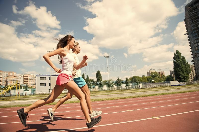 Couple of runners on sunny outdoor. Woman and man run on stadium. Activity and energy. Training and workout on fresh air royalty free stock photo