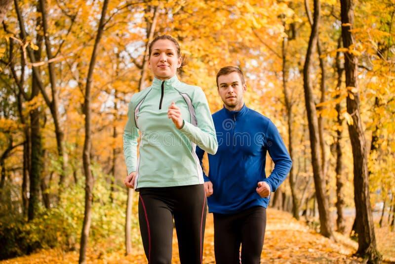 Couple running in autumn nature stock image