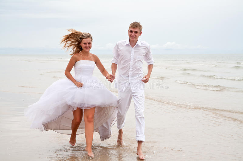 Couple running on a beach stock photos