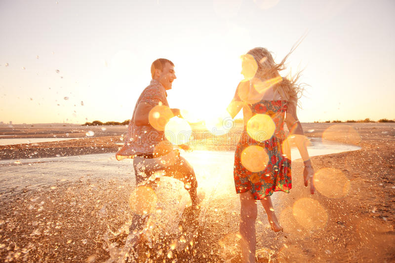 Couple running on the beach royalty free stock image