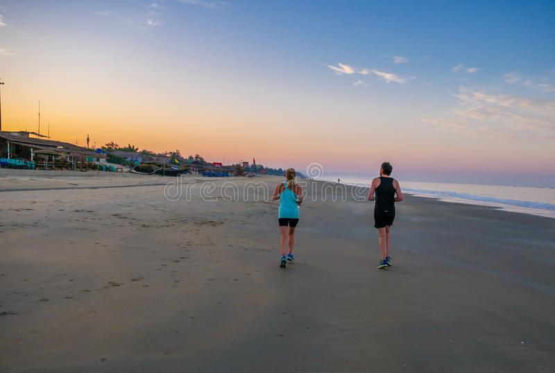 Couple running on the beach stock images