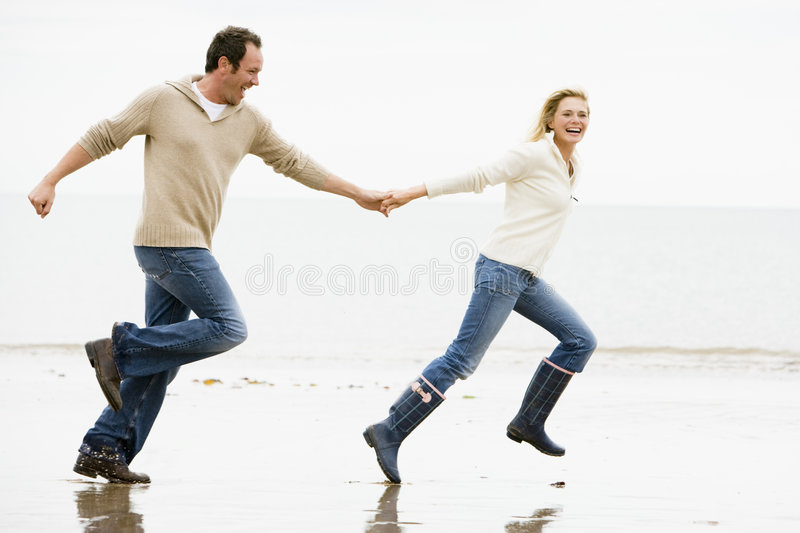 Couple running on beach holding hands royalty free stock photo