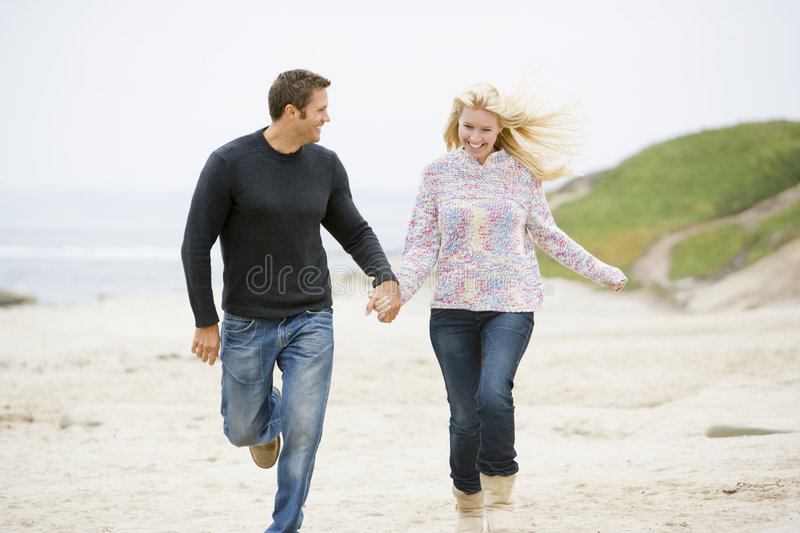 Couple running at beach holding hands