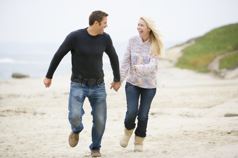 Couple running at beach holding hands royalty free stock image
