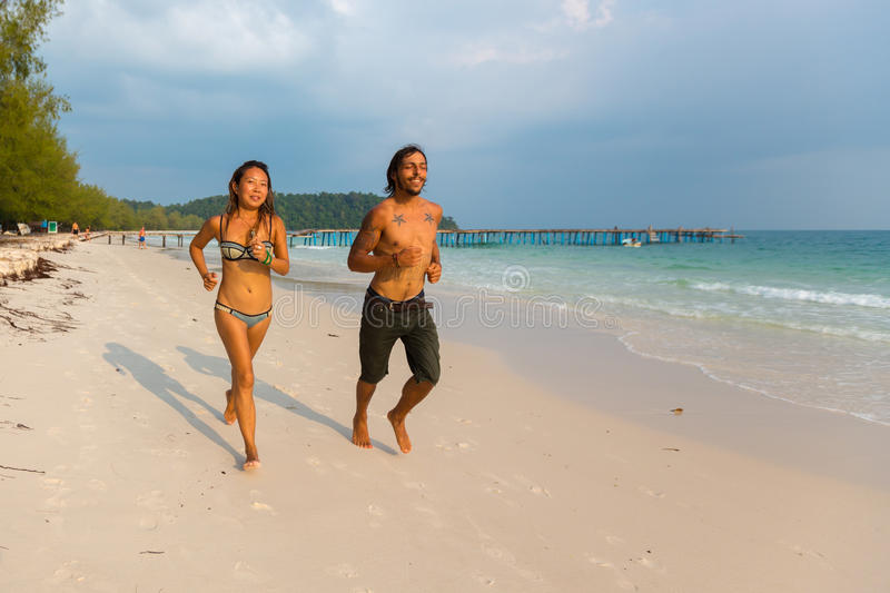 Couple running on the beach in Koh Rong Island, Cambodia stock photos
