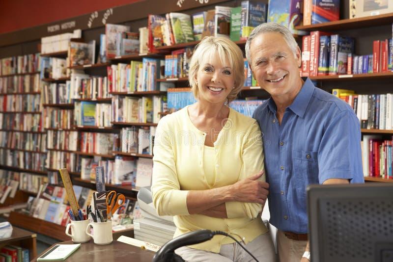Couple running bookshop. Looking cheerful royalty free stock photo
