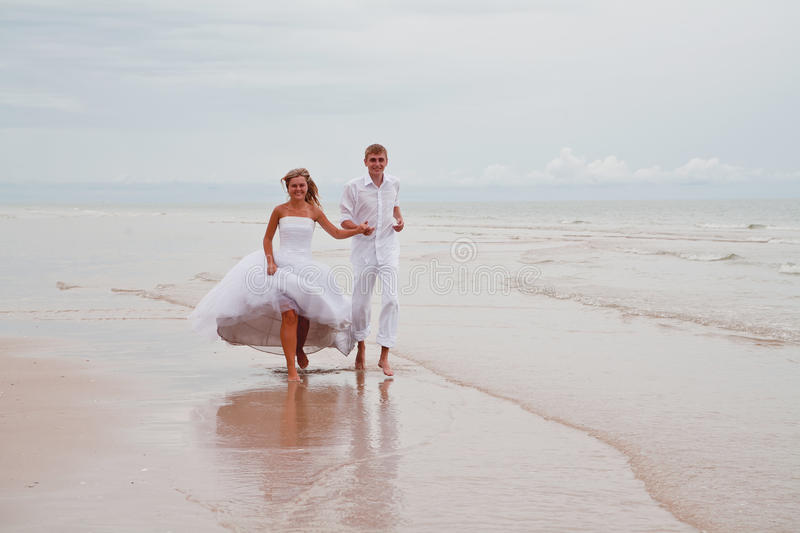 Couple running down a beach royalty free stock image