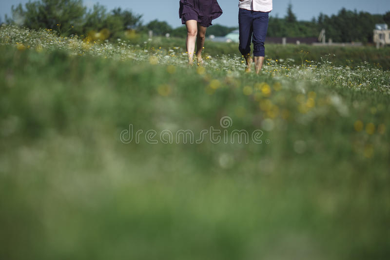 Couple running in field and have fun royalty free stock photography