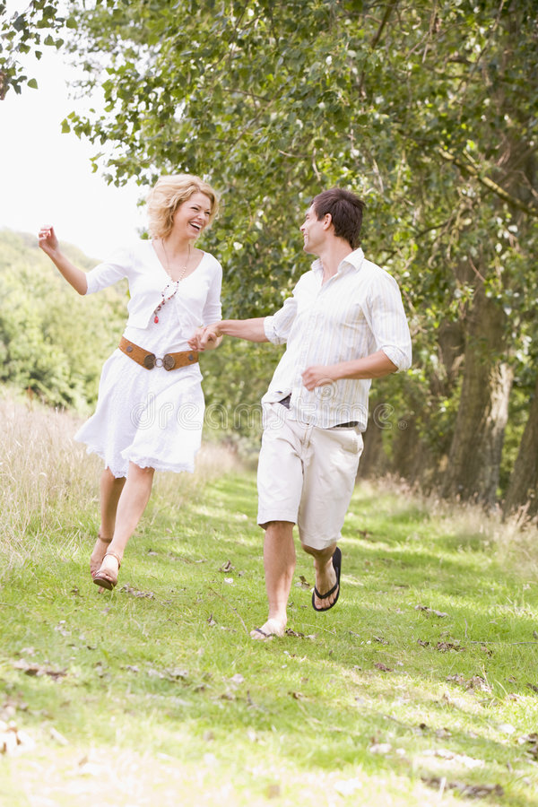 Free Couple Running On Path Holding Hands And Smiling Royalty Free Stock Photography - 5936907