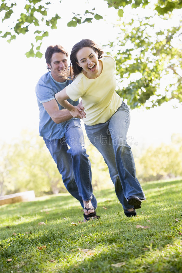 Download Couple Running Outdoors Holding Hands And Smiling Stock Image - Image: 5772021