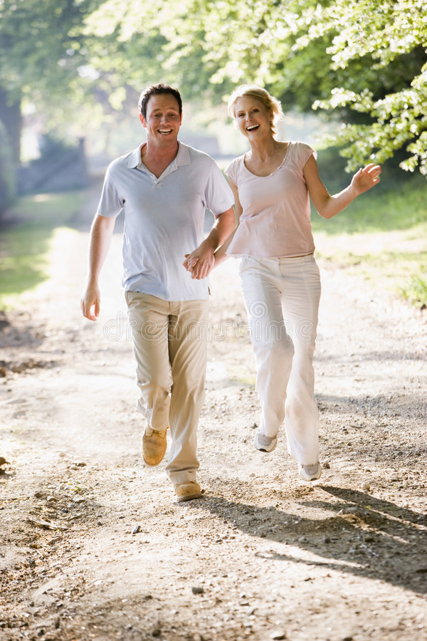 Download Couple Running Outdoors Holding Hands And Smiling Stock Image - Image: 5931447