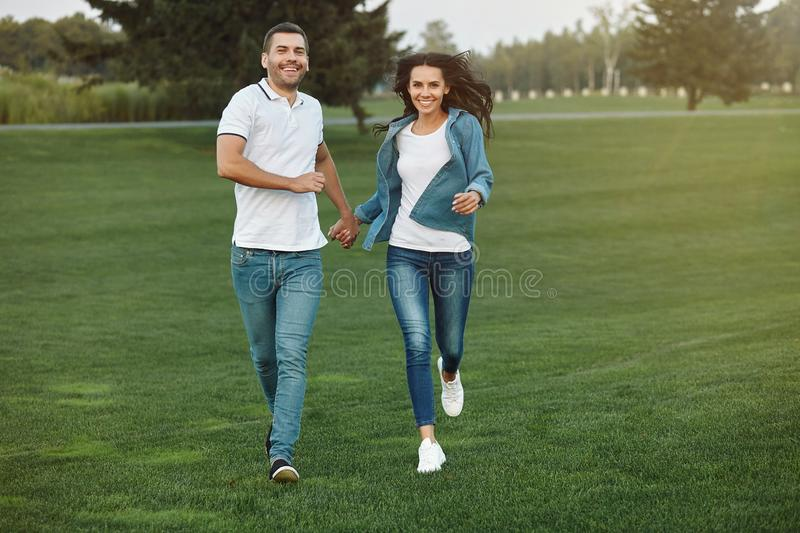 Couple running in the park at daytime. Full length shot of smiling couple running in the park at daytime stock images