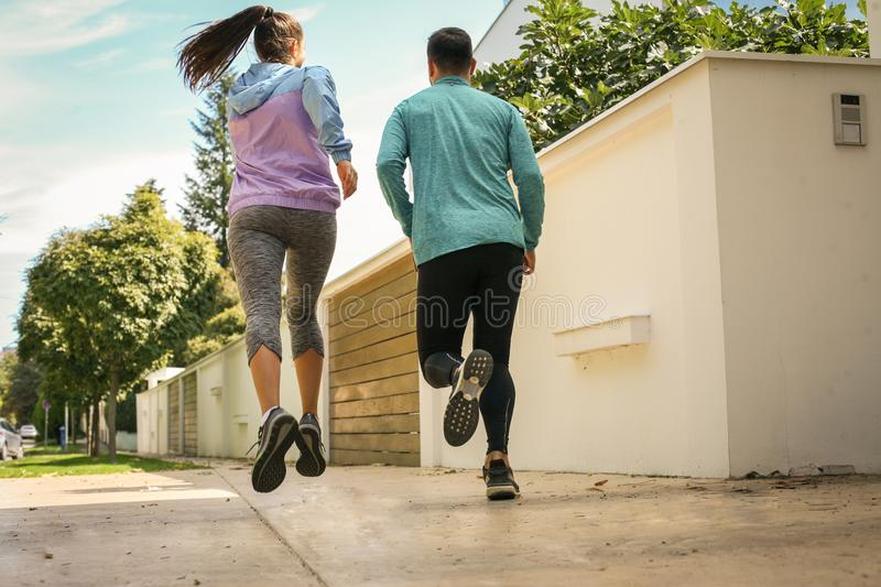 Couple running on sidewalk. From back. royalty free stock photography