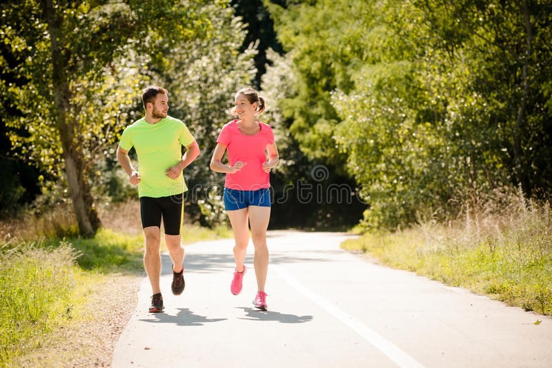 Couple running and talking together royalty free stock images