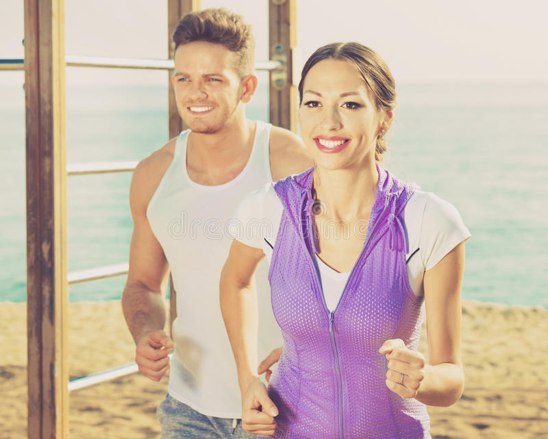 Download Couple Running Together On Beach By Ocean Stock Photo - Image of lifestyle, scene: 83702070
