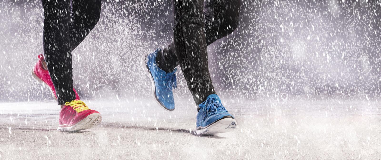 Couple running in winter. Athlete woman and man are running during winter training outside in cold snow weather