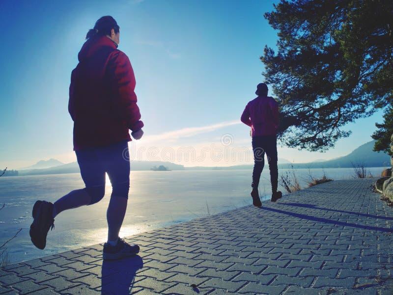 Couple runs through city park by lake shore stock image