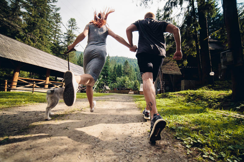 Couple runs on road in the nature with dog royalty free stock images
