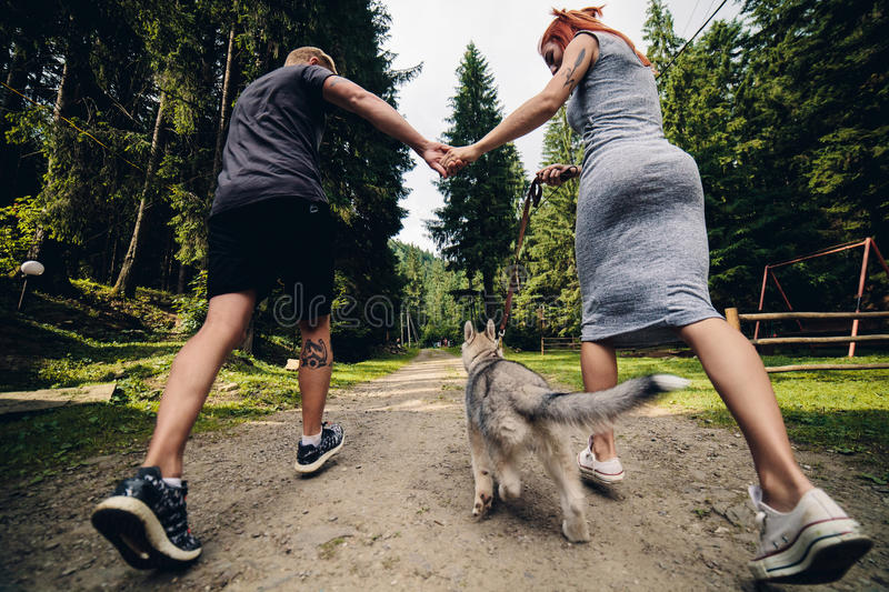 Couple runs on road in the nature with dog royalty free stock photography