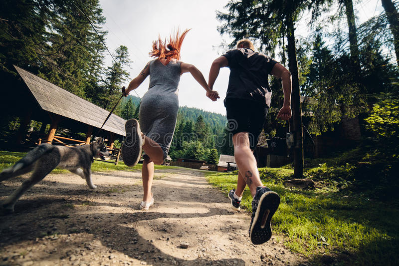 Couple runs on road in the nature with dog stock photo