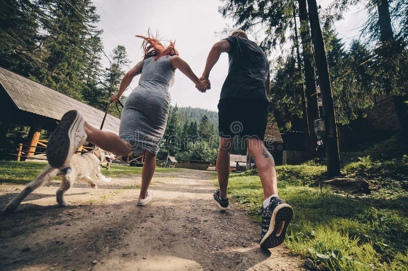 Couple runs on road in the nature with dog stock image