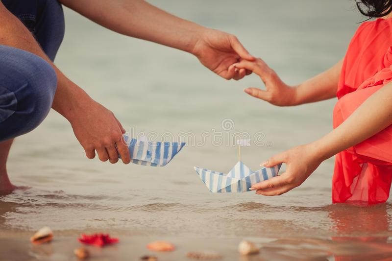 Couple`s hands with paper ships as a simbol of making a wish royalty free stock image