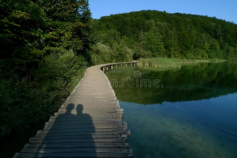 Couple's Shadow by a Lake royalty free stock photo