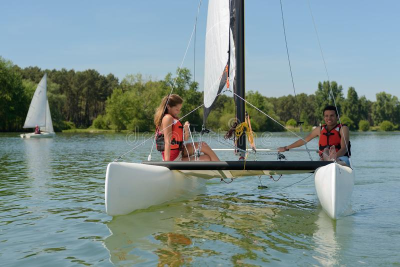 Couple sailing sailboat stock photography
