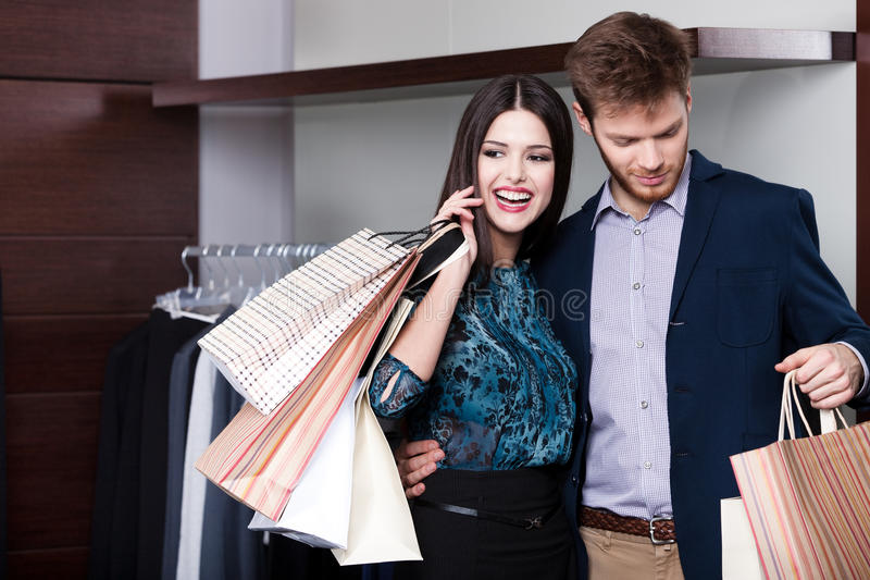 Couple is in the sale shop. Couple does shopping at the sale shop with great variety of clothes royalty free stock photos