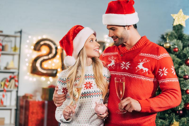 couple in santa hats with champagne glasses holding piggy bank with savings stock photo