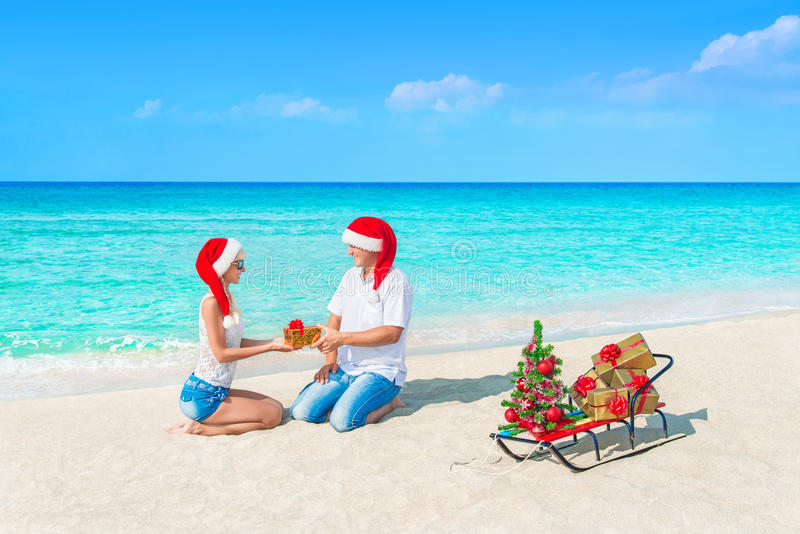 Couple in Santa hats at sea beach present Christmas gifts to each other with Happy New Year at tropical sandy beach. Lovers couple in Santa hats congratulated stock photo