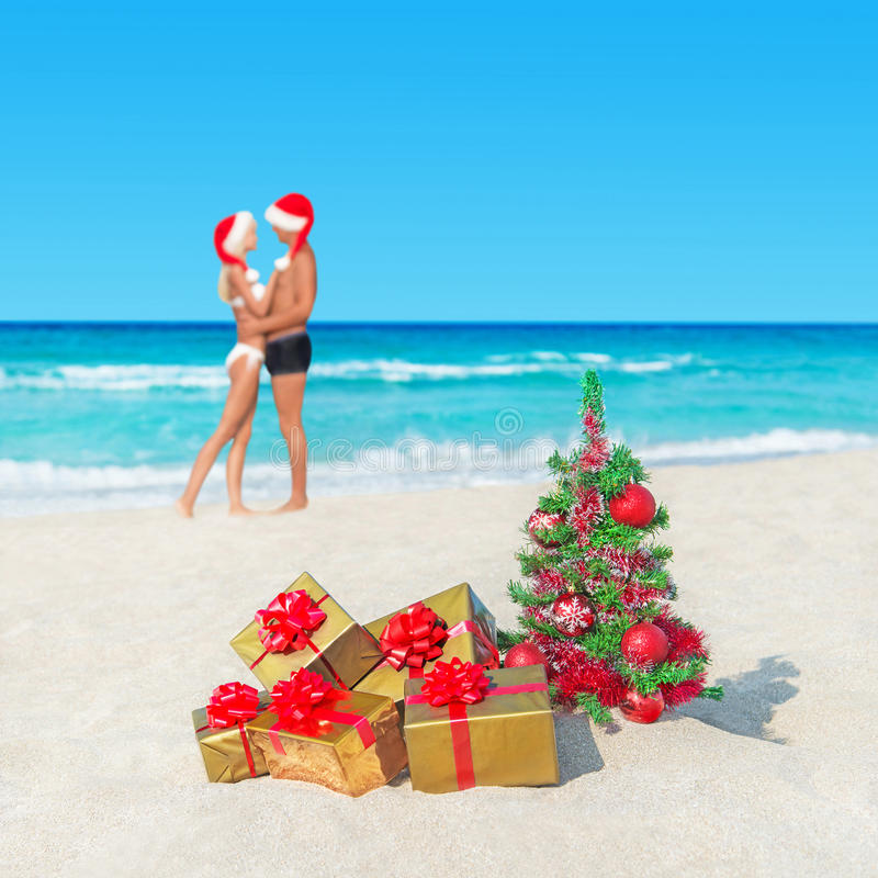 Couple in santa hats at tropical beach with christmas tree for Tropical vacations for couples