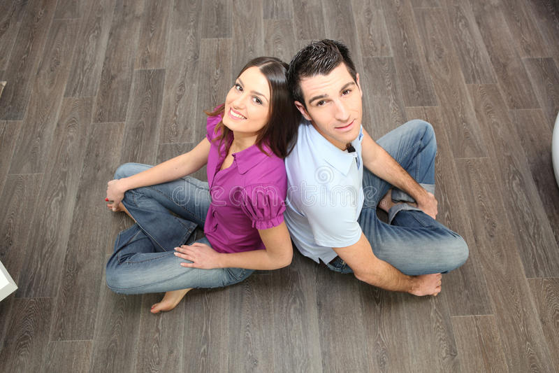 Couple sat on laminate flooring royalty free stock image