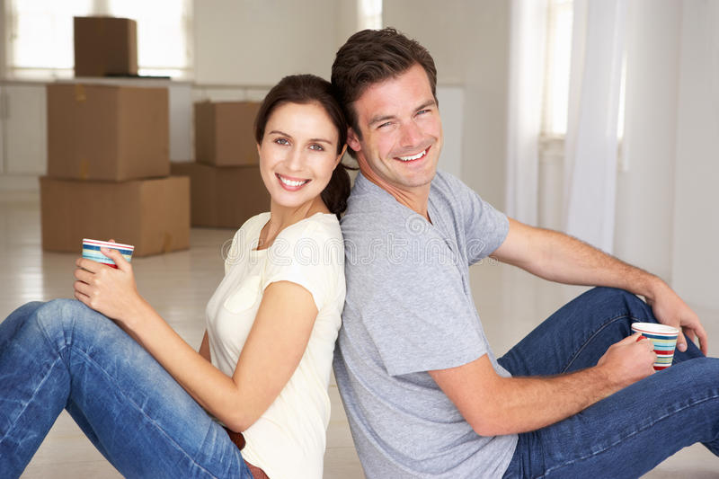 Couple sat in new home. Couple sat on floor in new home smiling at camera