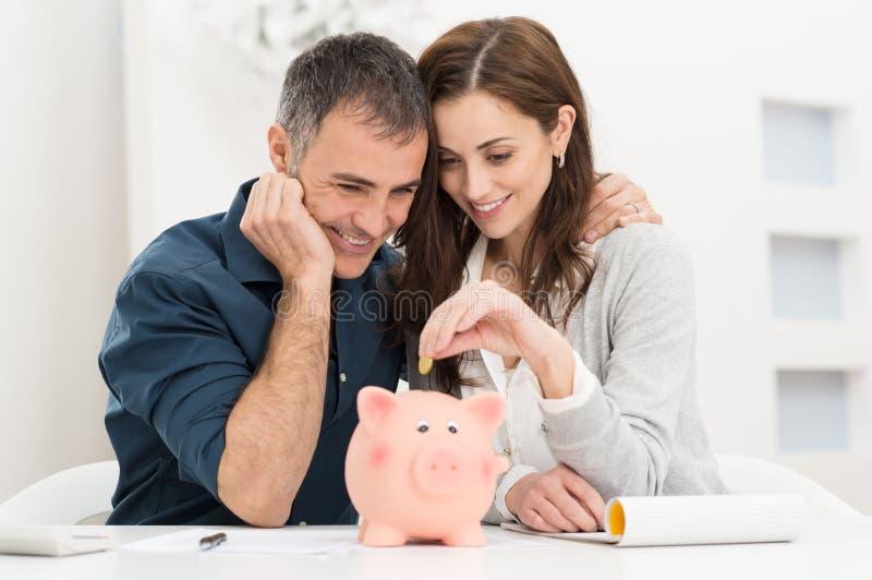 Couple Saving Money. Portrait Of Happy Couple Inserting Coin In Piggybank