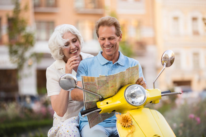 Couple on scooter is smiling. Mature men holding a map. This map is upside down. Jokes on the way home stock images