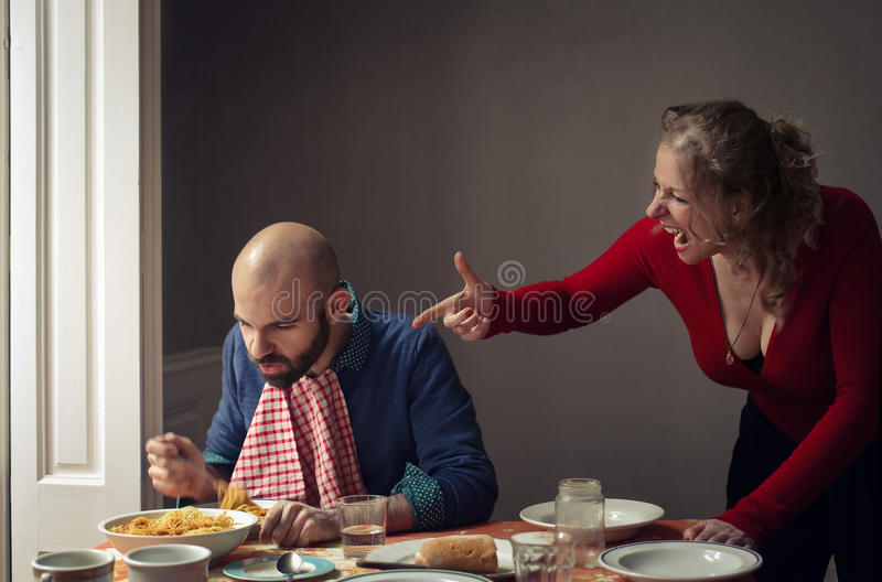 Couple screaming over a plate of spaghetti. Couple having lunch and women screaming and pointing at men over a plate of pasta while men is eating stock image