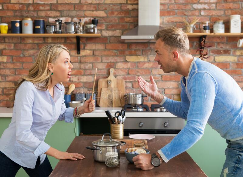 Couple screaming and shouting at each other in kitchen stock photo