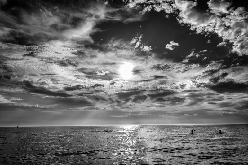 Couple in the sea. Black and white photo of the couple in the sea at the end of the summer under the cloudy sky royalty free stock photo