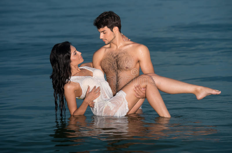 Couple in the sea. Passionate young couple in the sea stock photography