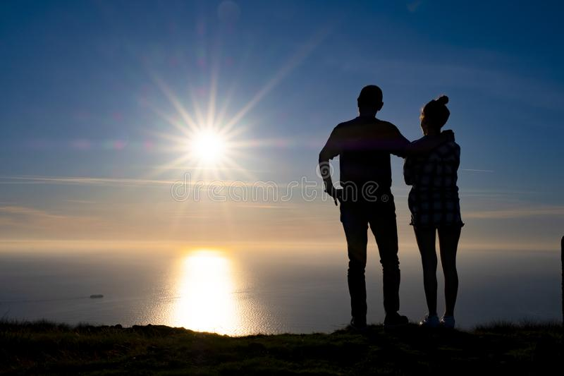 Couple with the sea and the sun at sunset stock photos